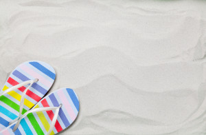 Colorful summer flip flops on white sand.